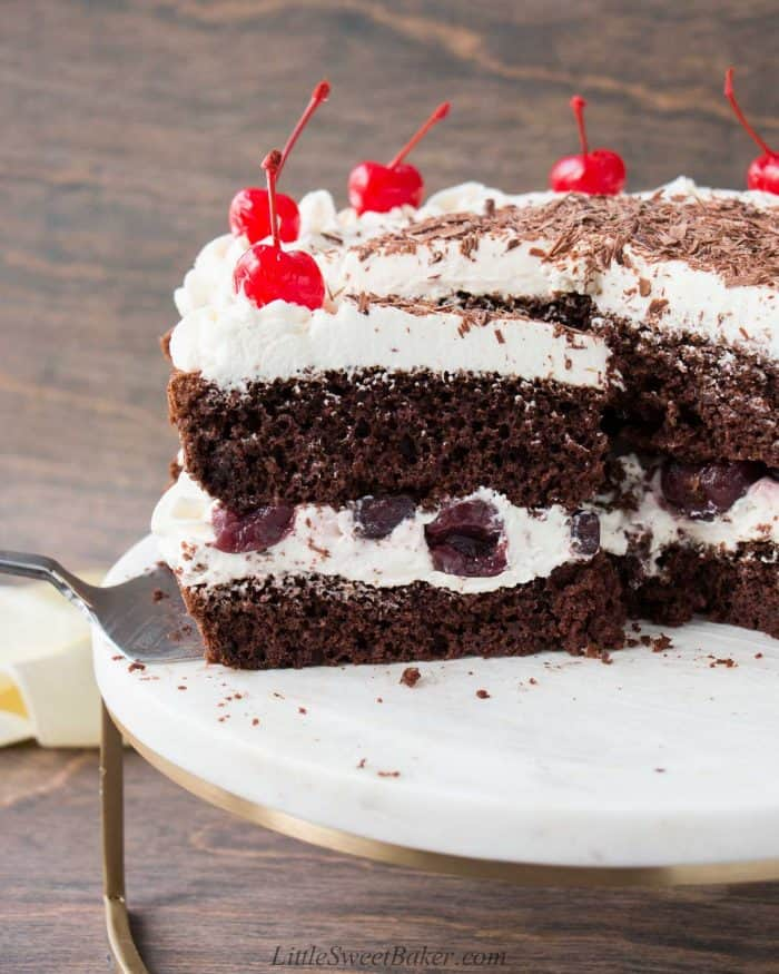 A slice of naked black forest cake being removed from the rest of the cake.