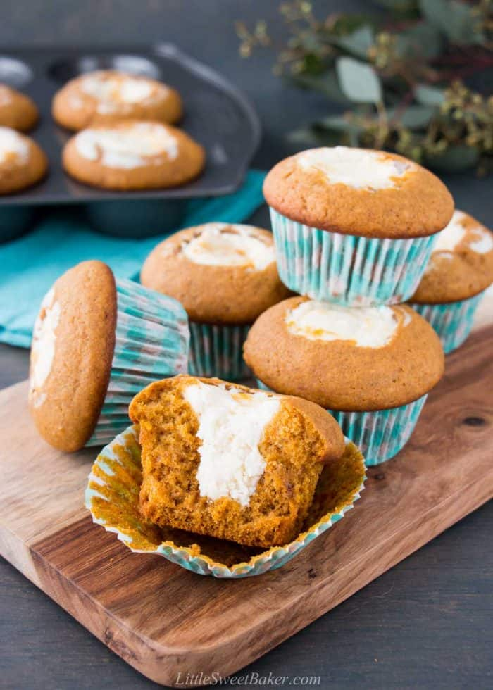 Pumpkin cream cheese muffins on a serving board with broken in half to show the inside.