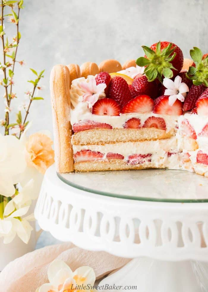 A cross section of a strawberry charlotte cake on a white cake stand.