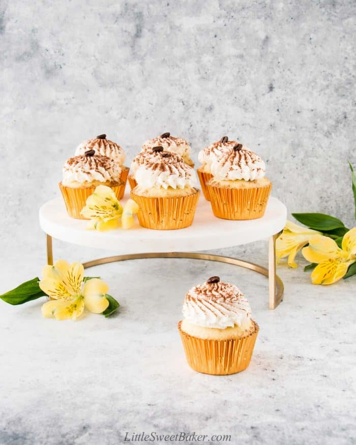 Tiramisu cupcakes on a gold and marble cake stand with yellow flowers.