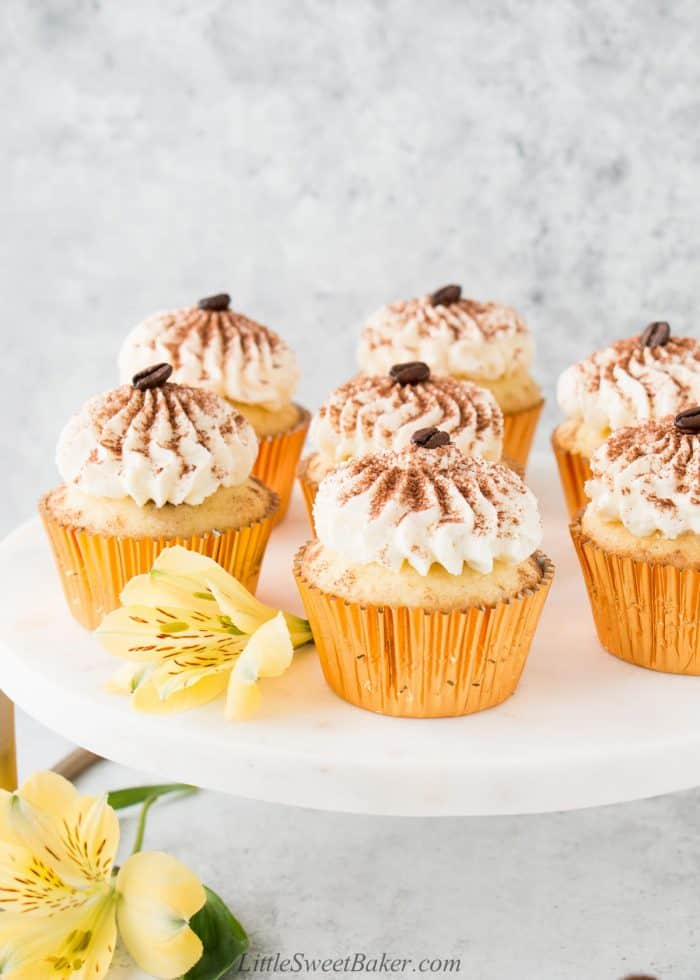Tiramisu cupcakes on a white marble stand with yellow flowers.