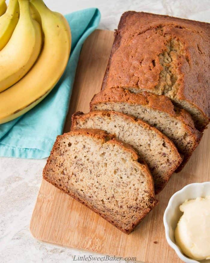 A loaf of moist banana bread on a cutting board.