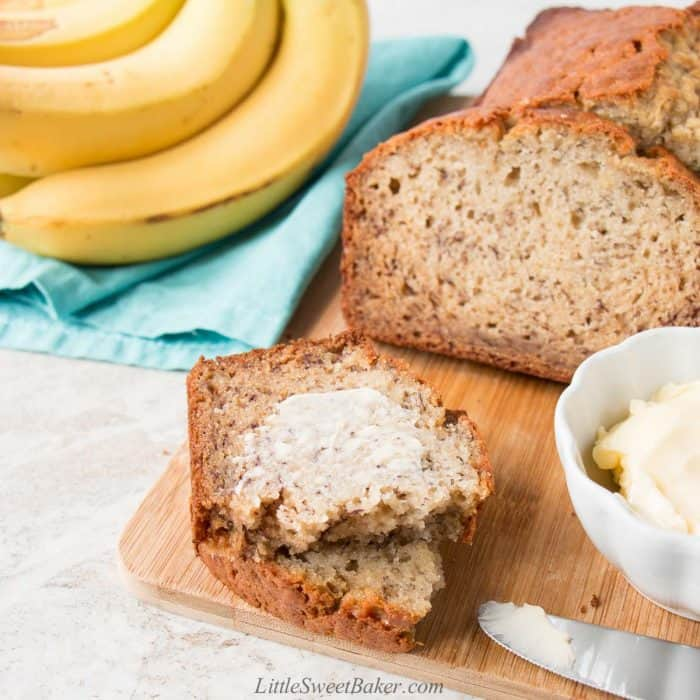 Banana bread on a cutting board with a buttered slice.