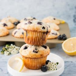 Two blueberry lemon muffins staked on a white plate.