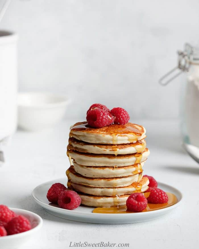 A stack of pancakes with maple syrup and raspberries.