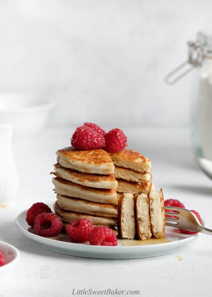 A stack of cut pancakes on a white plate with raspberries.