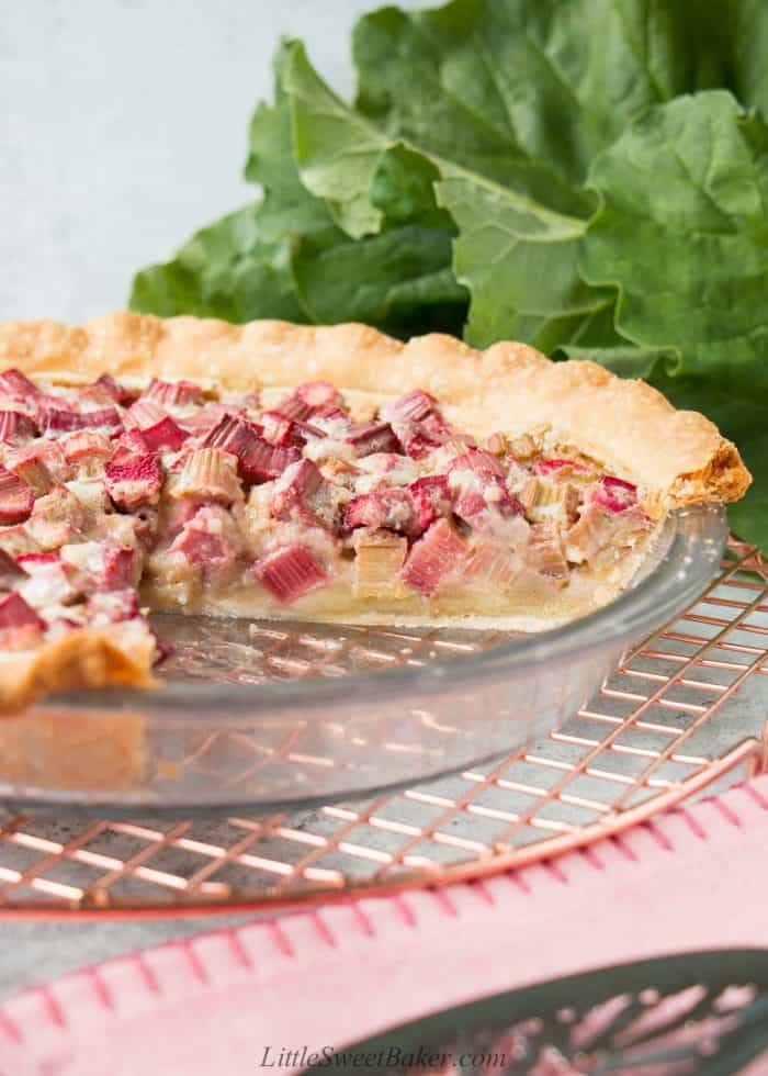 An eye-level view of a rhubarb custard pie with a slice cut out.