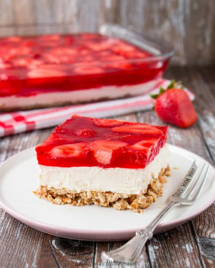 A slice of strawberry pretzel salad on a white and pink plate.