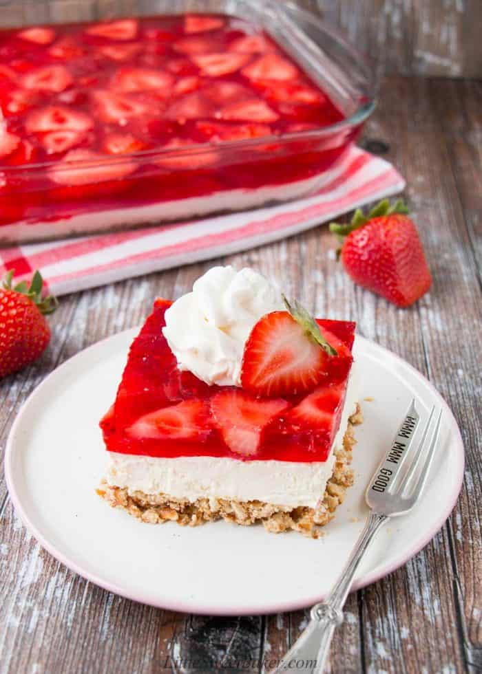 A slice of strawberry pretzel salad topped with whipped cream and half a strawberry.