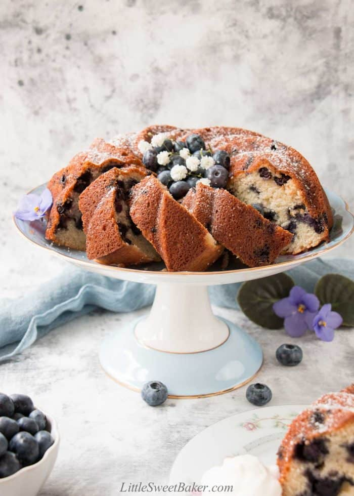 A blueberry bundt cake partially sliced on a blue cake plate.