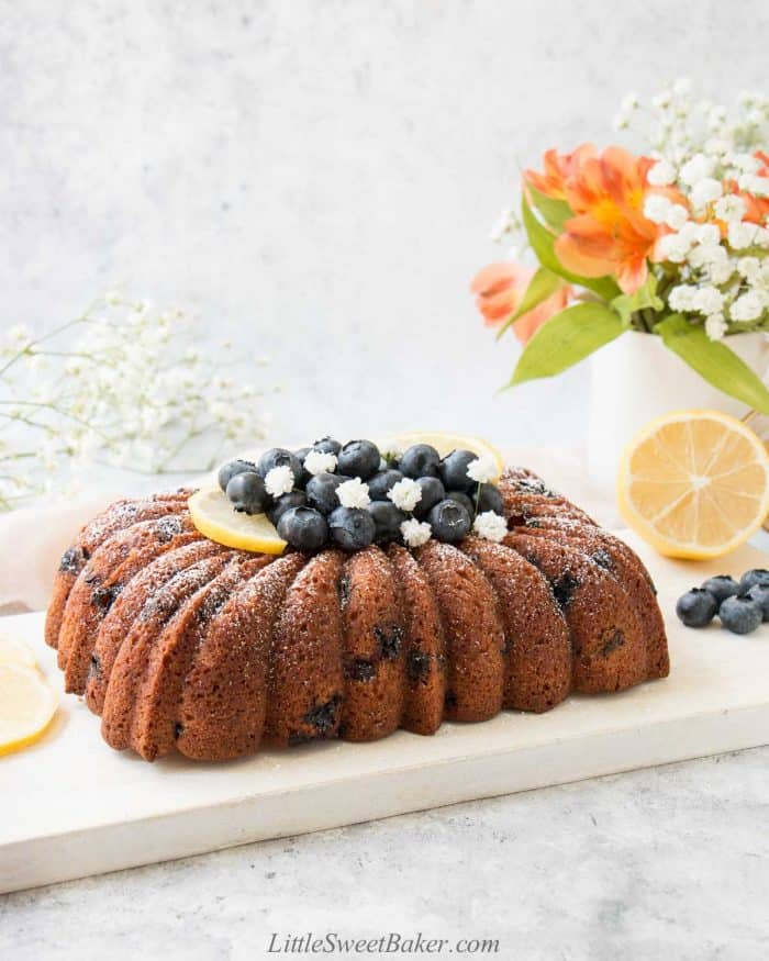 A loaf of lemon blueberry pound cake with blueberries, lemon, and white flowers on top.