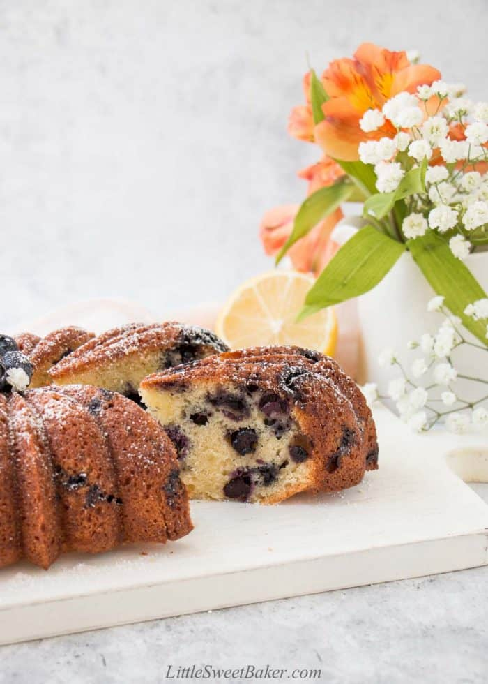 A slice of lemon blueberry pound cake pulled from a loaf on a white board.