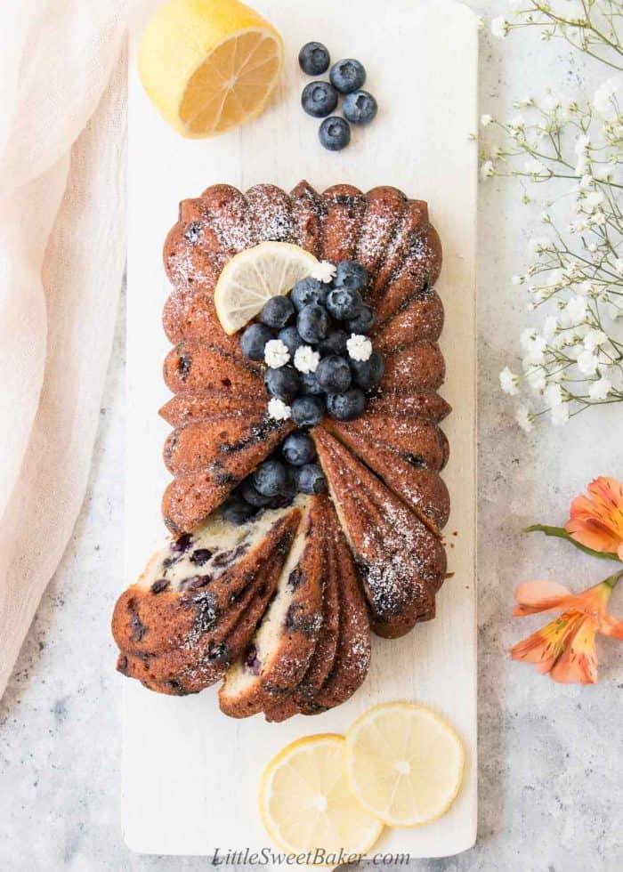 A loaf of lemon blueberry pound cake on a white board.