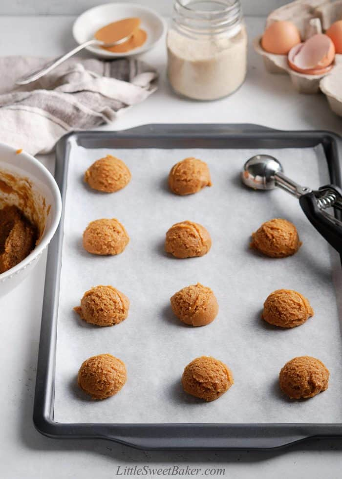 Unbaked healthy peanut butter cookies on a baking tray.
