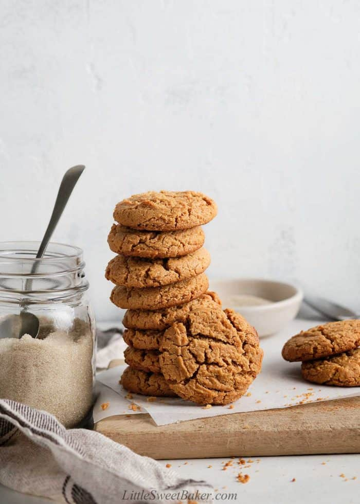 A stack of healthy peanut butter cookies on a wooden board.