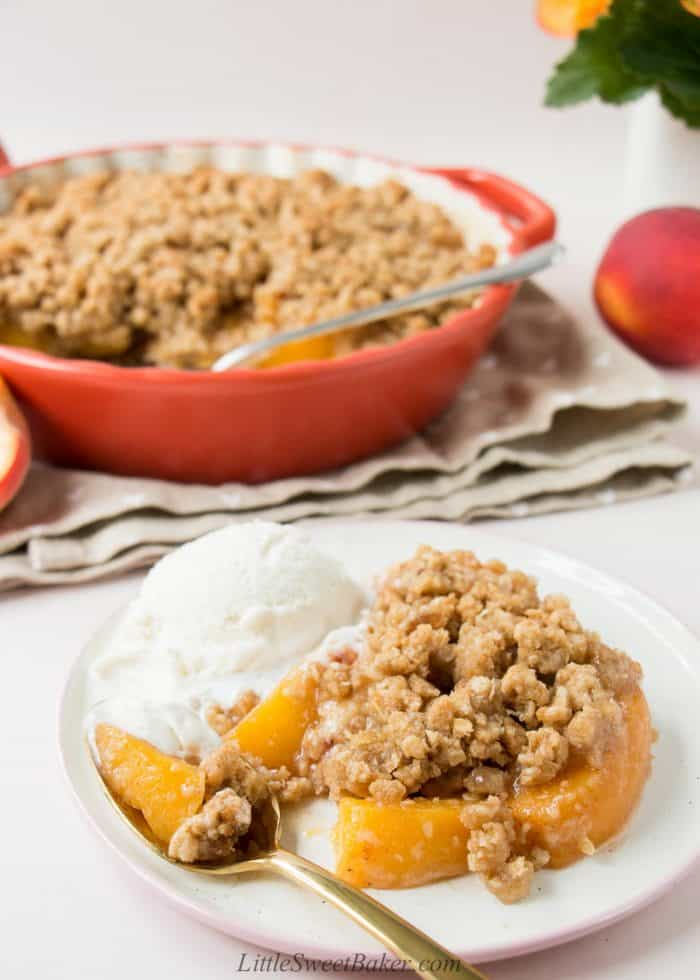 Peach crisp on a plate with a scoop of melty vanilla ice crean