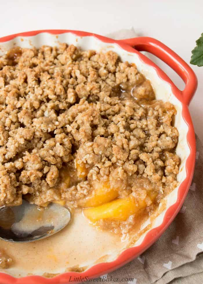 Peach crisp in a round serving dish with a few scoops missing.