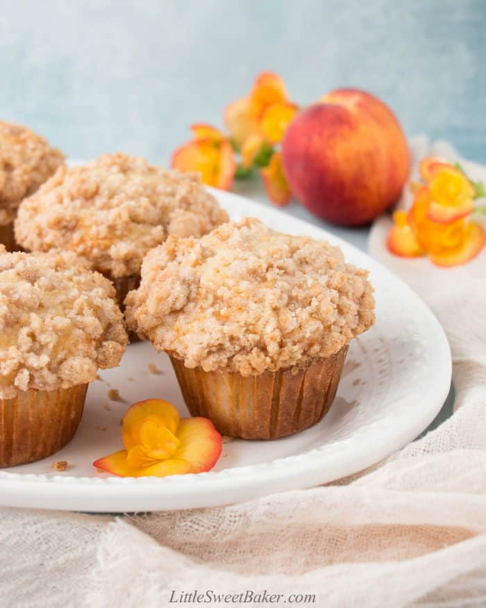 Peach crumb muffins on a white plate with a peach and flowers in the back.