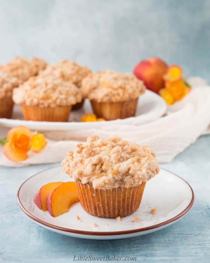 Peach muffin with crumb topping on a plate with two peach slices.