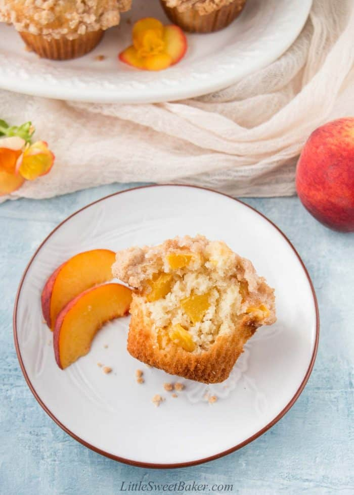 A peach crumb muffins with a big bite missing on a plate.