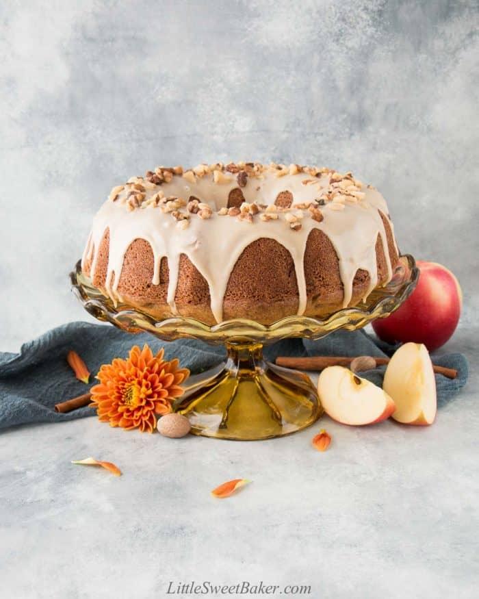 Apple bundt cake with maple glaze on a vintage cake stand.