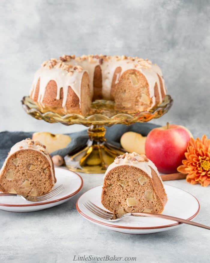 Apple bundt cake on a cake stand with two slices on plates.