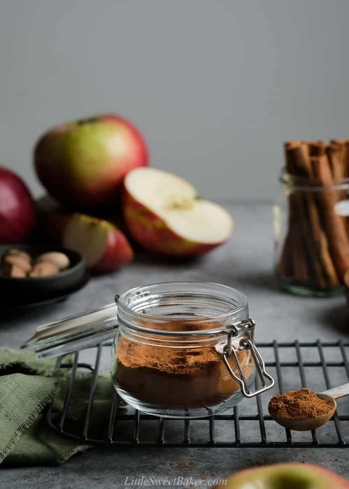 An open jar of apple pie spice on a cooling rack with apples and cinnamon sticks in the background.