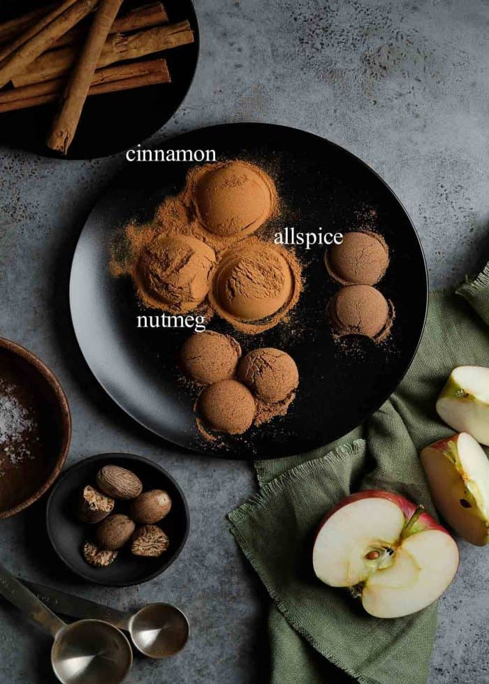 A black plate with clumps of cinnamon, allspice and nutmeg to show all the ingredients in apple pie spice.