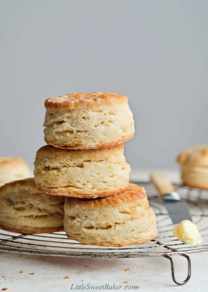 A stack of flaky butter biscuits on a cooling rack.