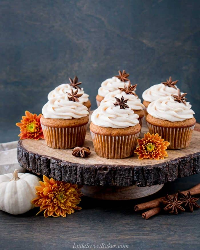 Pumpkin cupcakes with cream cheese frosting on a wooden cake stand.