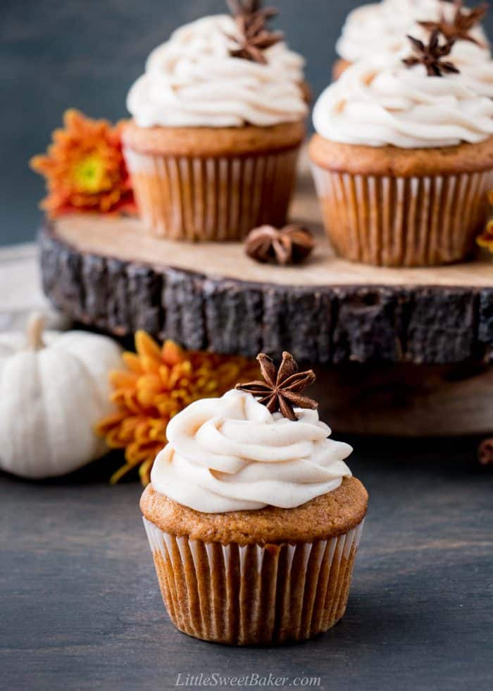 A pumpkin cupcake infront of a wooden cake stand with pumpkin cupcakes.