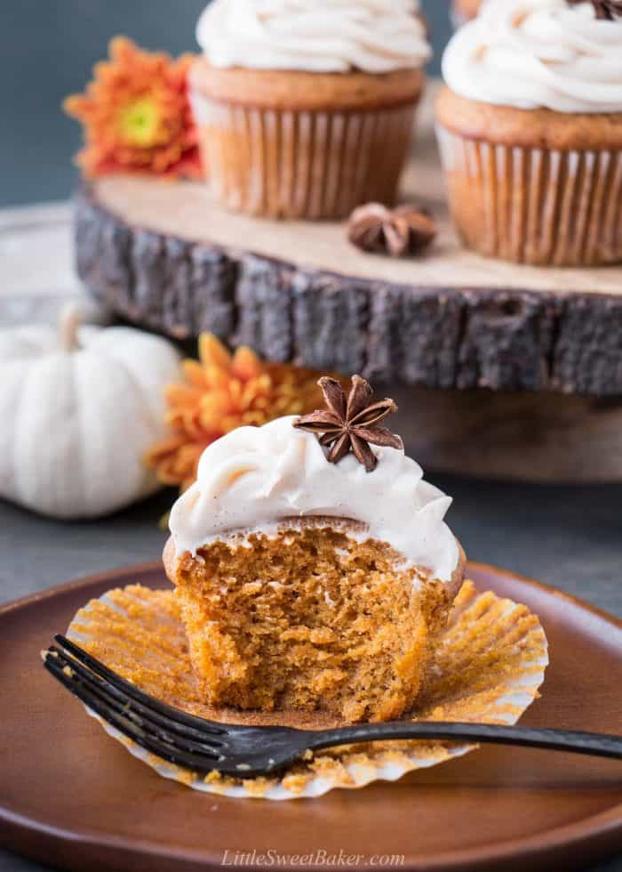 A pumpkin cupcake cut in half on a wooden plate with a fork.