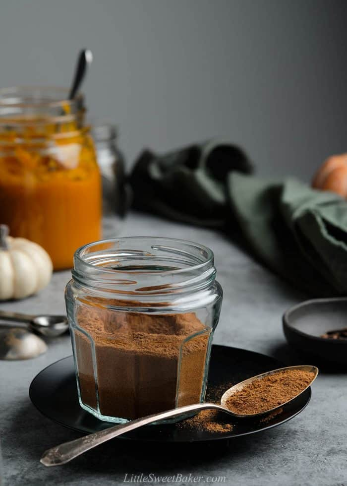 A jar of pumpkin pie spice mix on a black plate with a spoon.