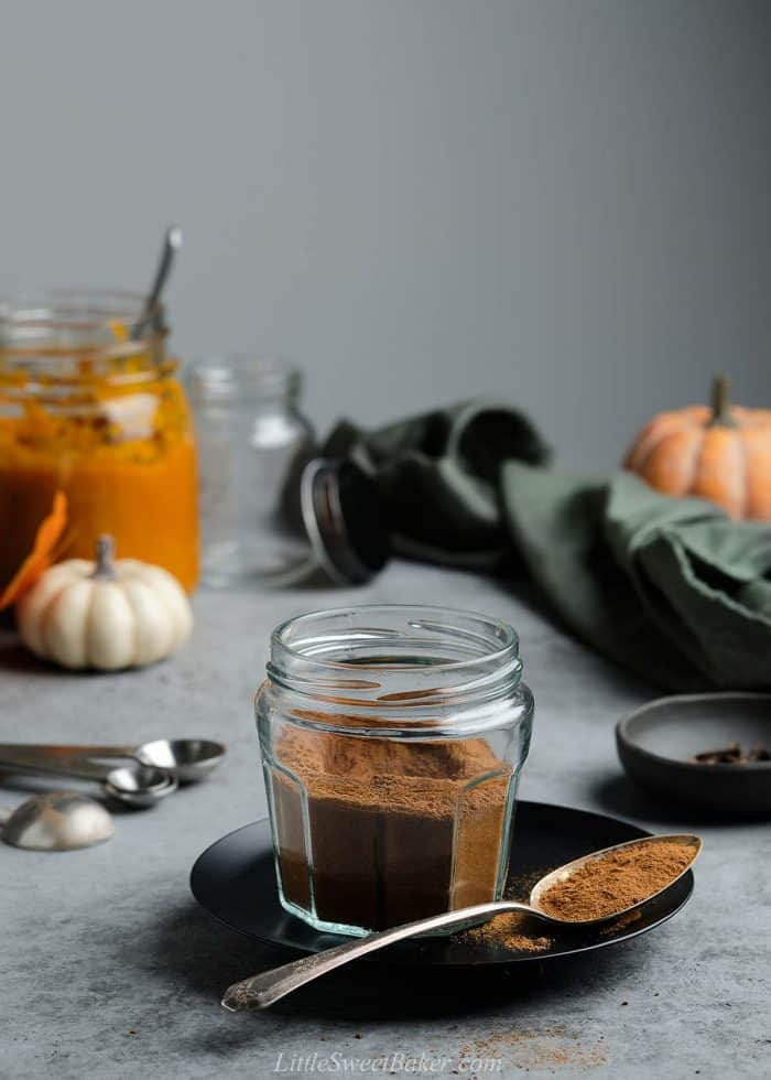 A open jar of pumpkin pie spice on a black plate with a spoonful.