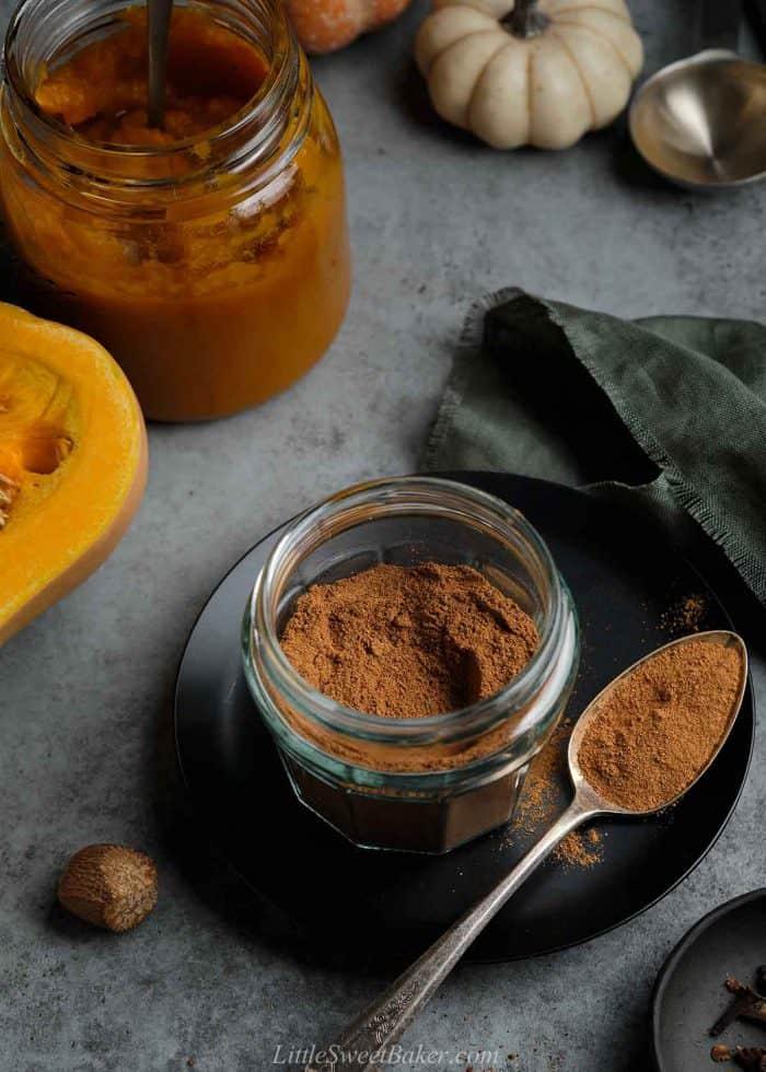 A open jar of homemade pumpkin pie spice mix on a black plate.