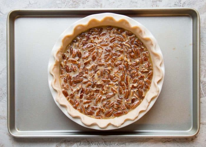 An unbaked pecan pie on a cookie sheet.