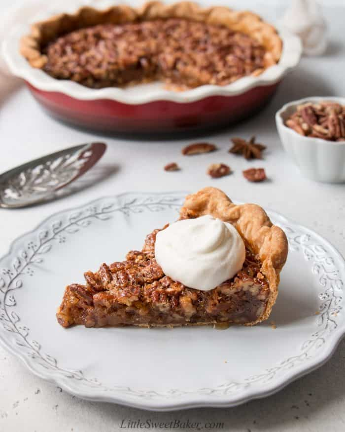 A slice of pecan pie topped with whipped cream in a light grey plate.