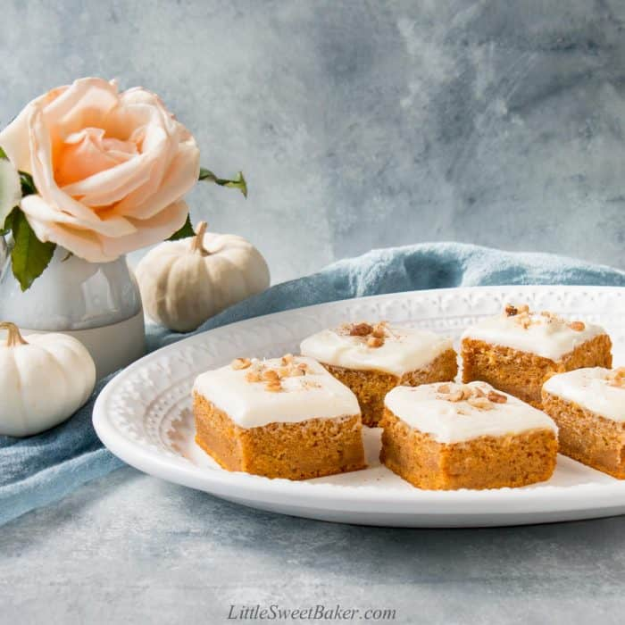 Pumpkin bars topped with cream cheese frosting and walnuts on a white oval serving plate.