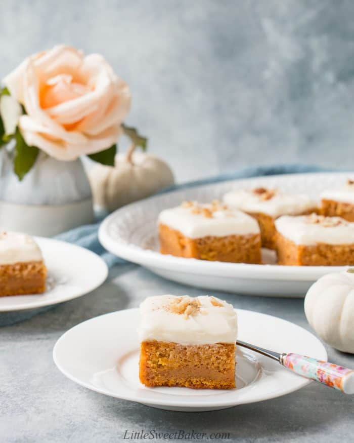 Two pumpkin bars on white plates and four on a serving plate.