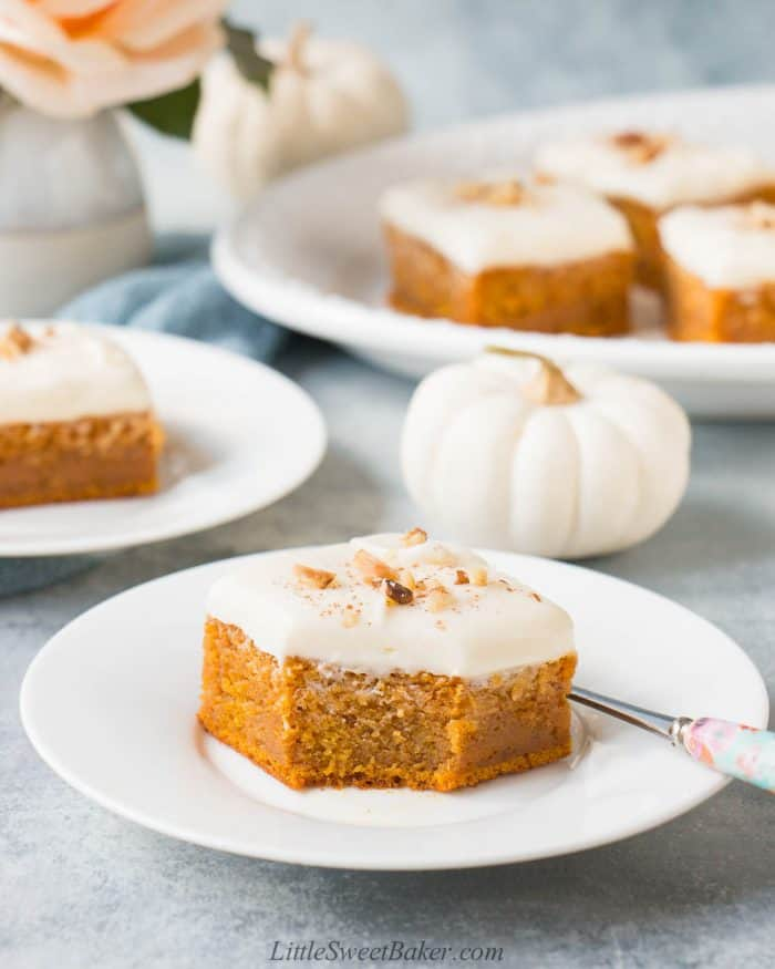 A slice of pumpkin bar with cream cheese frosting on a white plate.